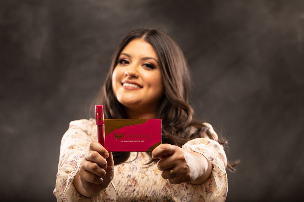 Leslie Valdivia, smiling, in front of a studio backdrop and holding products from her makeup company Vive Cosmetics