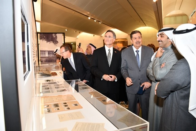 Four men looking at documents in a museum exhibit